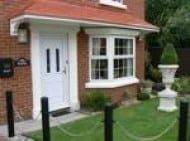 White door with a canopies above it finished in red brick similar to the walls of the house