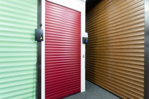 green and red roller shutters and brown panelled garage door