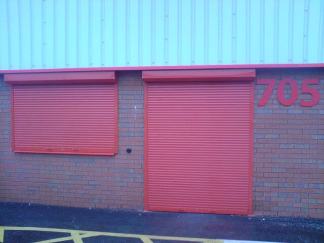 Closed red exterior roller shutters with lt garage doors