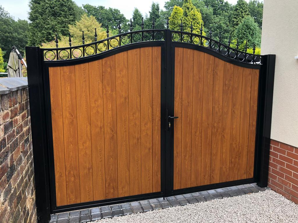 Timber infill driveway gate is styled with a wrought iron top, powder coated black.