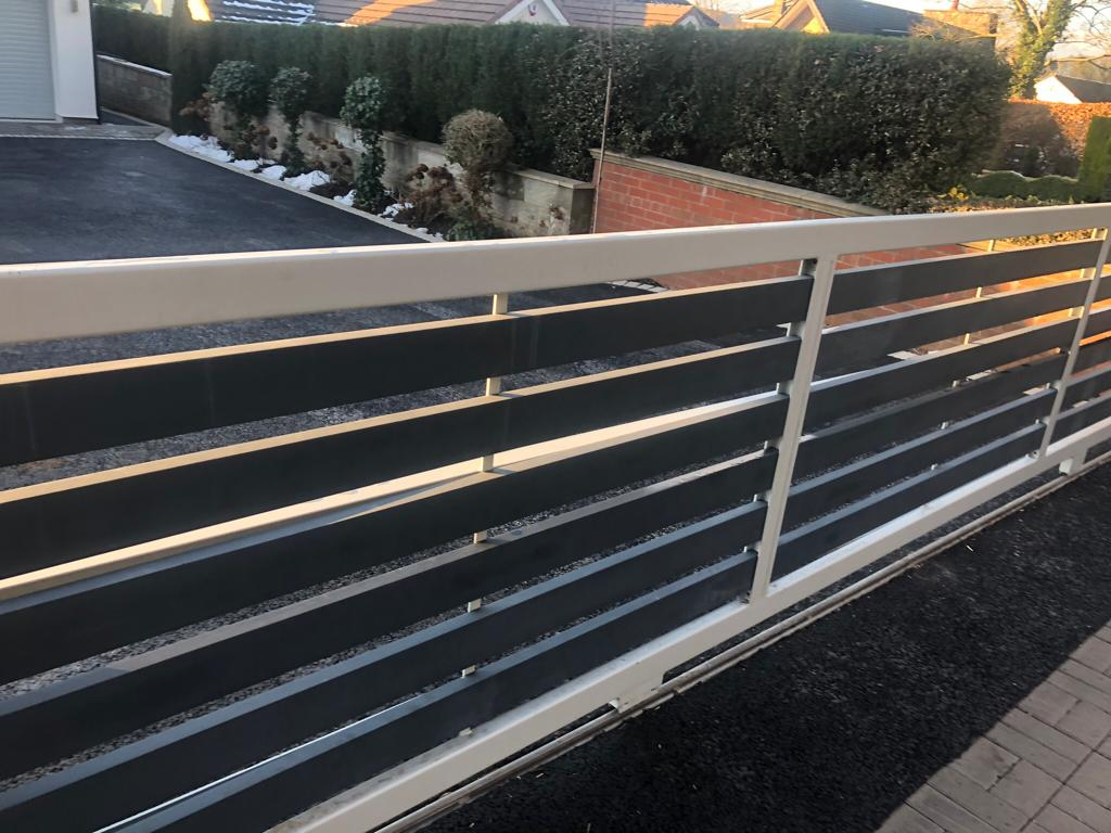 A modern powder coated driveway gate with horizontal slats and vision spaces