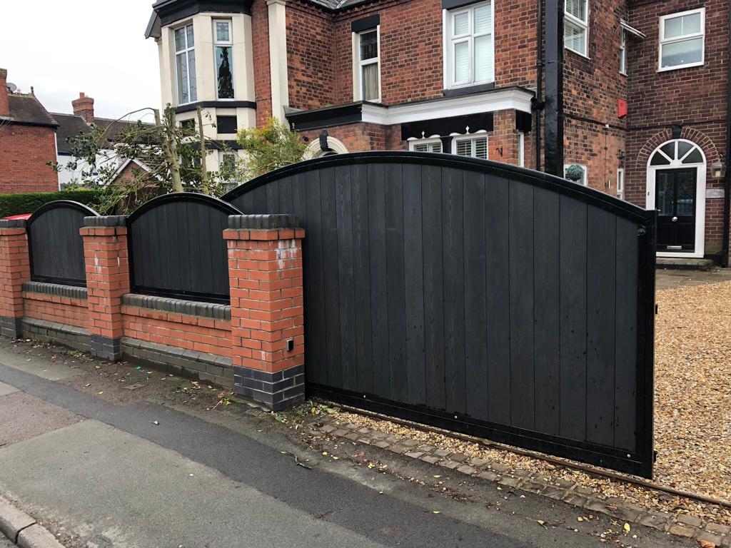 An automated composite infilled driveway gate in a vertical pattern with fence panels to match