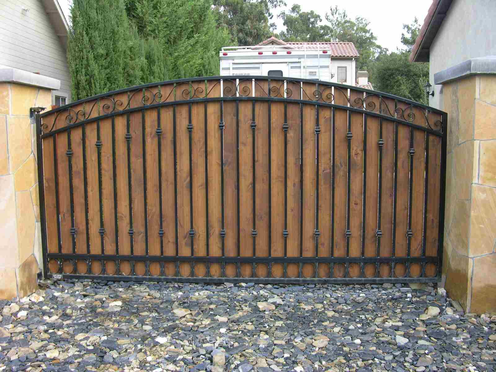 A timber infill driveway gate with a wrought iron finish
