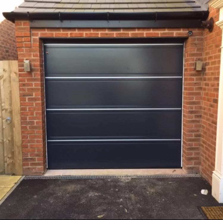 Hormann T ribbed sectional garage door in anthracite grey smooth finish panels, with a brushed stainless steel infill decoration.