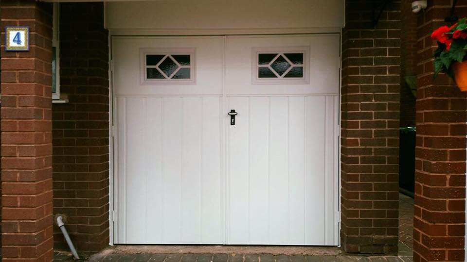 A pair of Fort side hinged garage doors 50/50 split and powder coated white and in the Chester medium vertical rib with the Waterford windows.