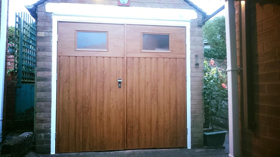 A pair of 50/50 split side hinged garage doors with windows in a vertical pattern