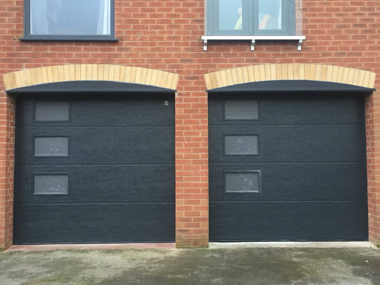 2 x black sectional garage doors in an L ribbed pattern with windows