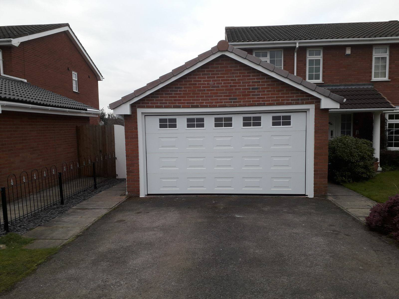1 x double sectional garage door in a Georgian pattern, powder coated with decorative glazing cross windows. Finished off with a white surround to match