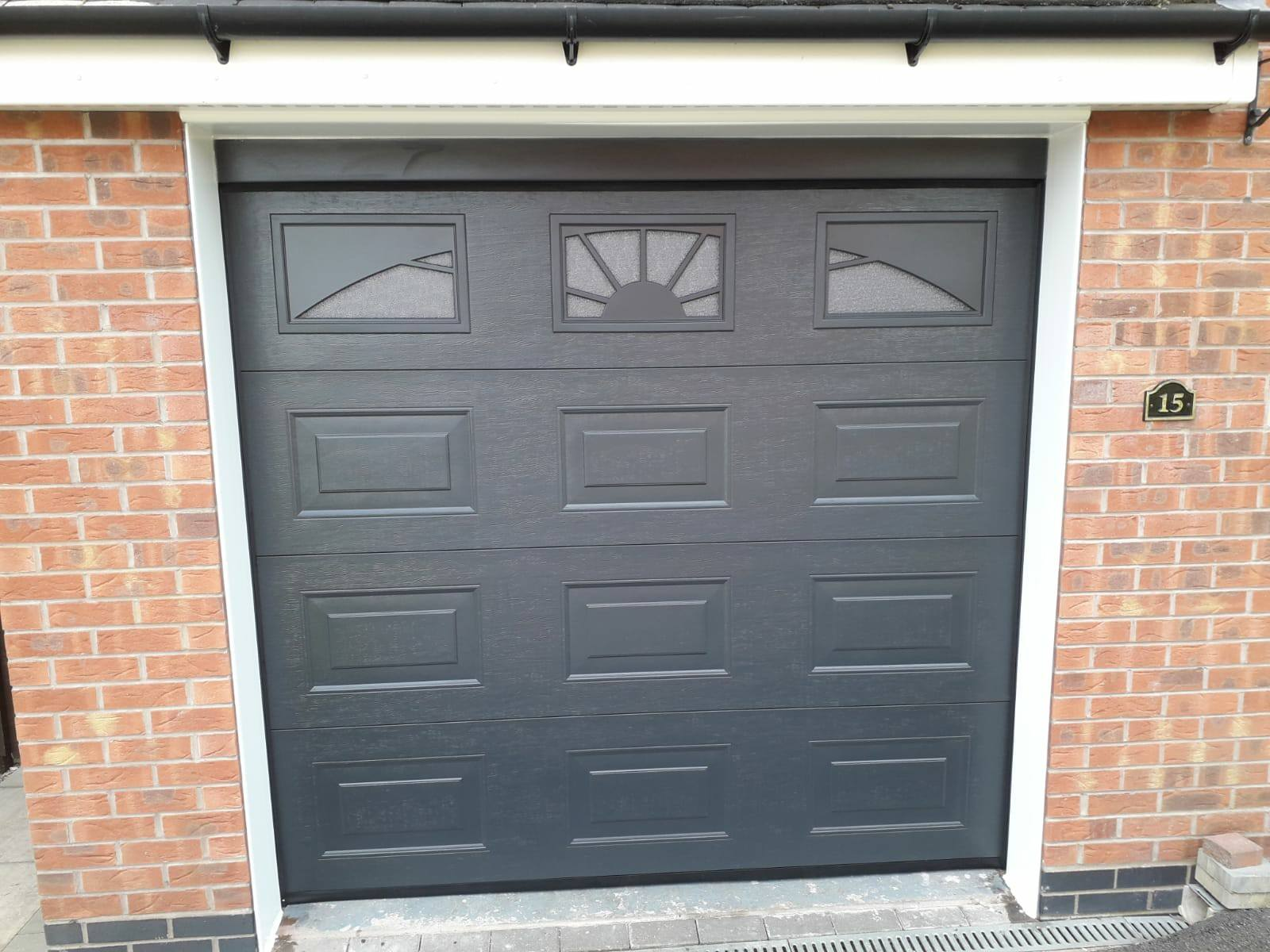 1 x single sectional garage door, powder coated anthracite grey in a woodgrain finish with sunrise windows