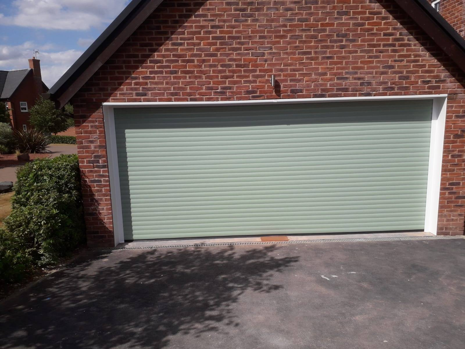 1 x double roller garage door in a chartwell green finish with a white surround