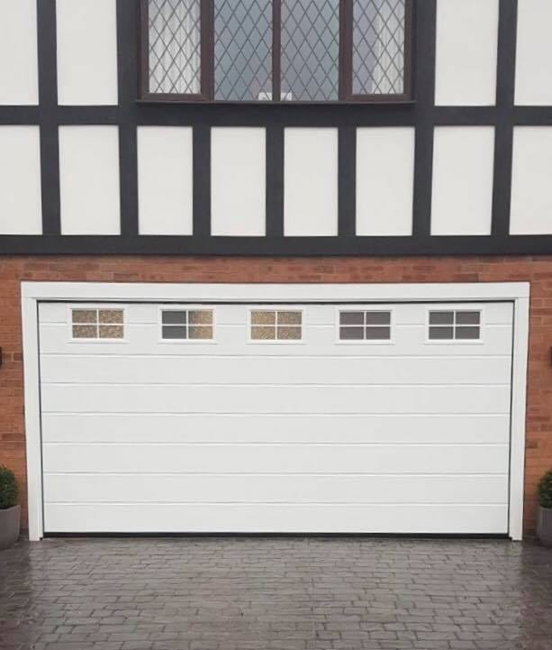 Electric Alutech sectional garage door with 5 frosted windows across the top panel, M-Ribbed pattern in white operated by NRG Black Edition motor complete 2x remote controls