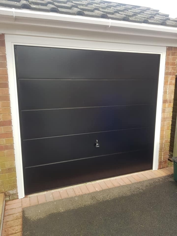 Garador up & over garage door in the ascot design finished in black with a white frame supplied and installed