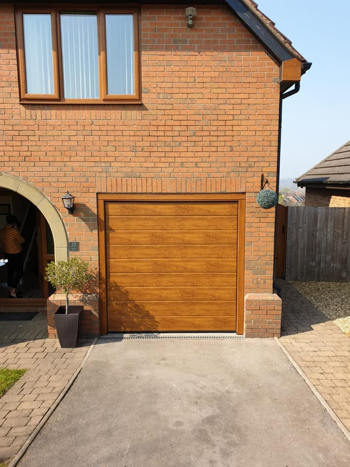 A single Alutech sectional garage door in an M ribbed pattern and oak finish