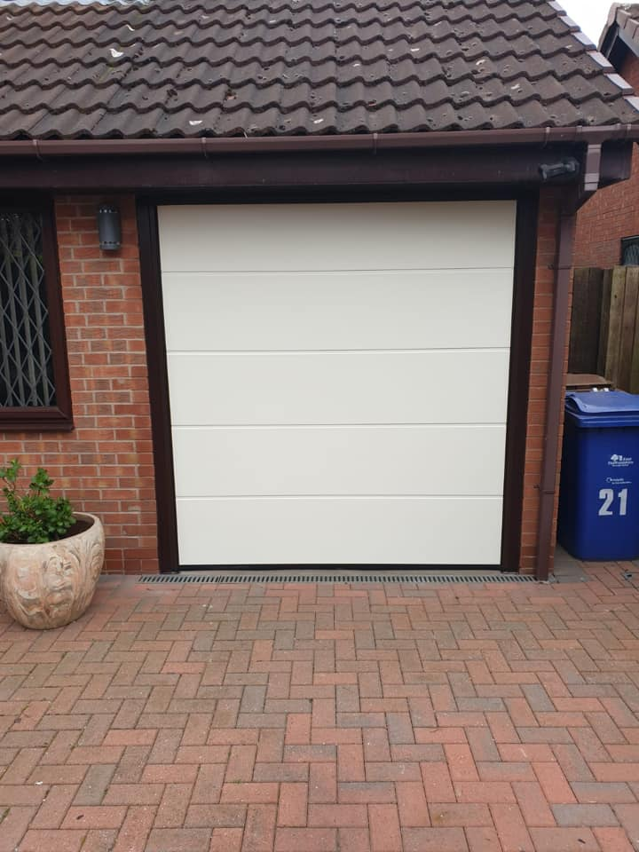 1 x single sectional garage door from the Alutech range in an L ribbed pattern, powder coated cream with a brown surround.