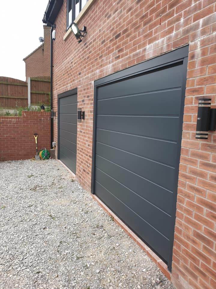 Two M ribbed, Alutech sectional garage doors powder coated in anthracite grey with a matching surround