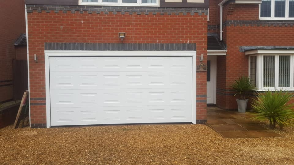 1 x Alutech sectional garage door. Georgian design in white with a wood-grain finish. Electrically operated via 1 x sectional motor. Complete with 2 remote handsets.