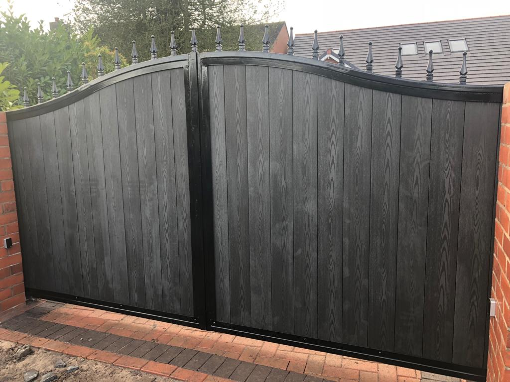 This grand composite infill motorised driveway gate has been finished off with a wrought iron top and powder coated black