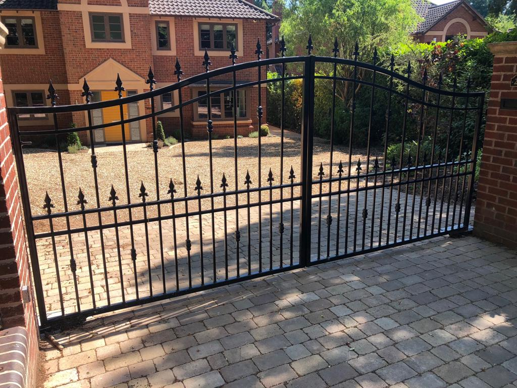 An automated, galvanised, wrought iron, powder coated black driveway gate
