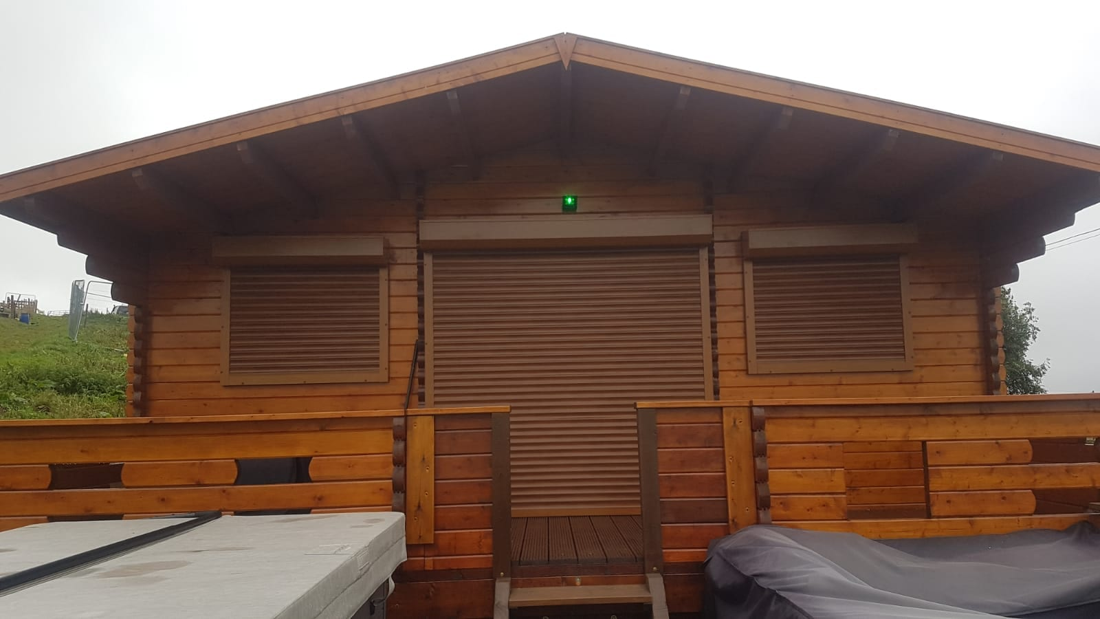 Golden oak door and window security shutters fitted on a log cabin with a surround to match
