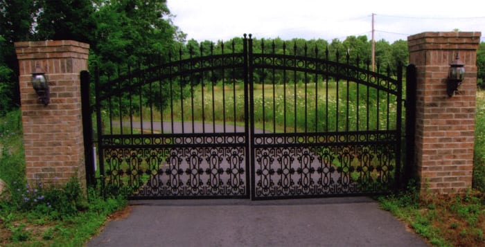 An automated galvanised driveway gate, powder coated black on wrought iron, fitted to two brick pillars