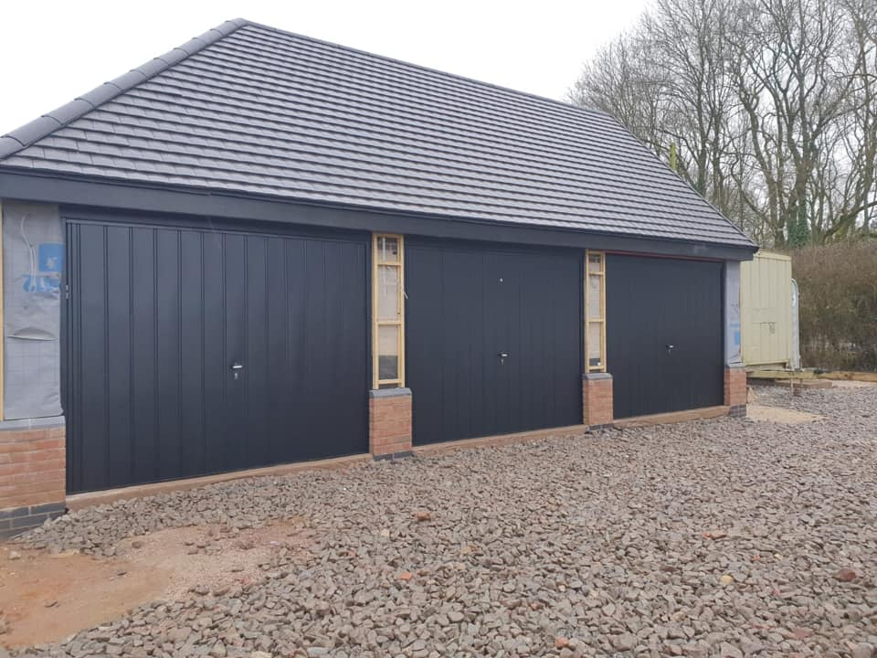 3 x Fort retractable framed up and over garage doors in a medium vertical design. Powder coated black with a matching surround.