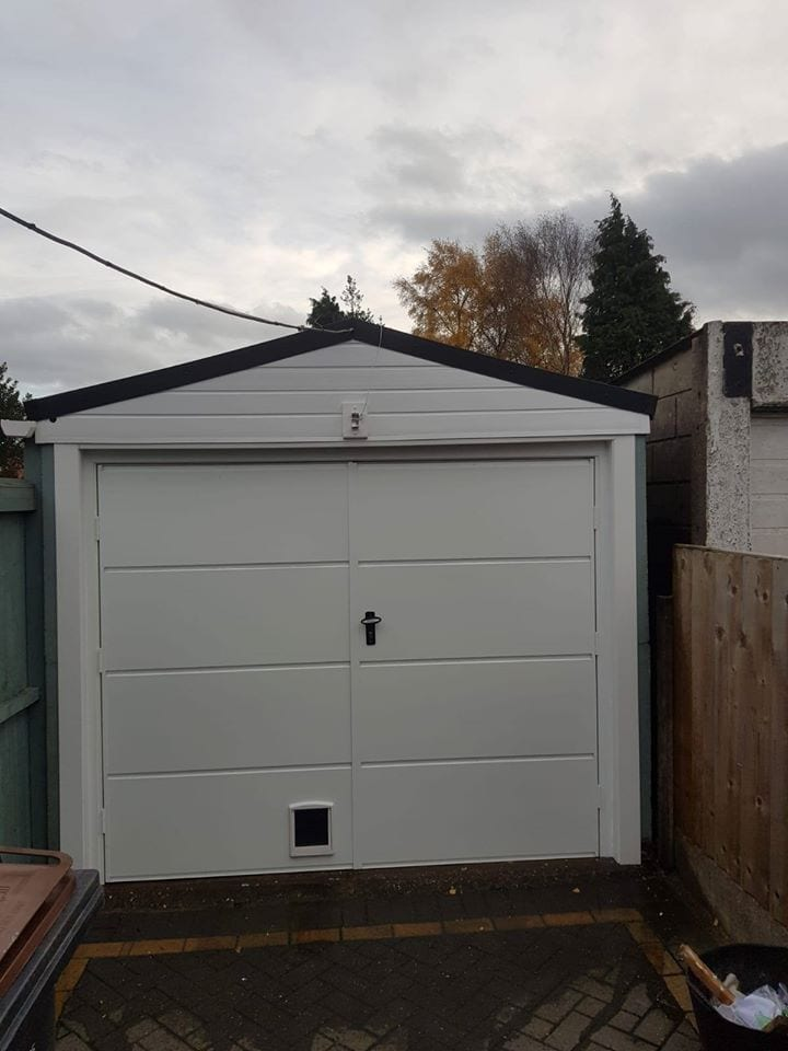 A set of white Fort side hinged garage doors in the wide rib design with a 50/50 split. This door also has an added feature of a pet flap to the bottom left (viewed from outside).