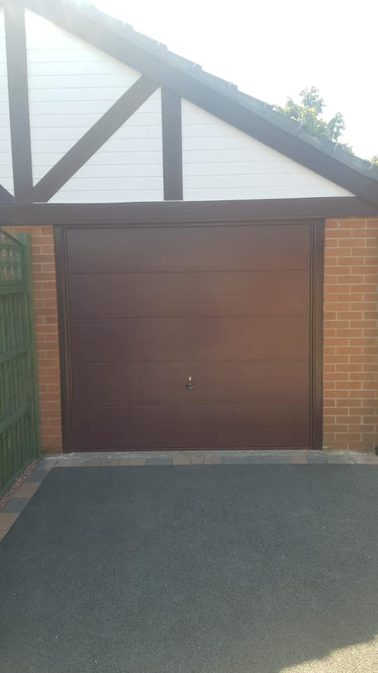 Garador canopy framed up and over garage door in the Wentwood design. Finished in Rosewood with a matching surround