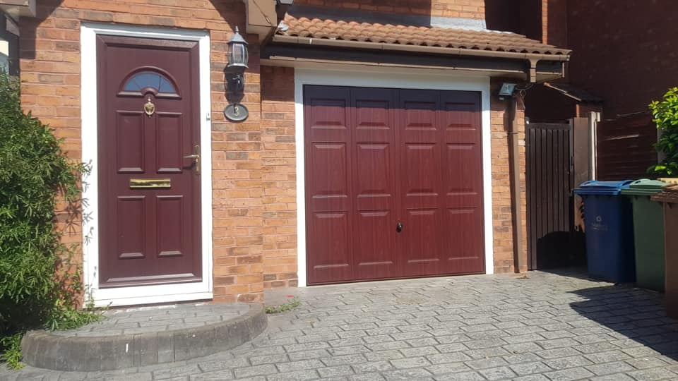 Hörmann retractable up and over garage door in the Georgian design. Finished in rosewood with a white surround