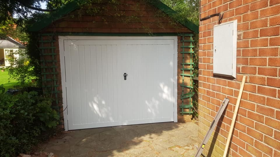Fort retractable in a Georgian design up and over garage door with a powder coated white finish and a matching frame