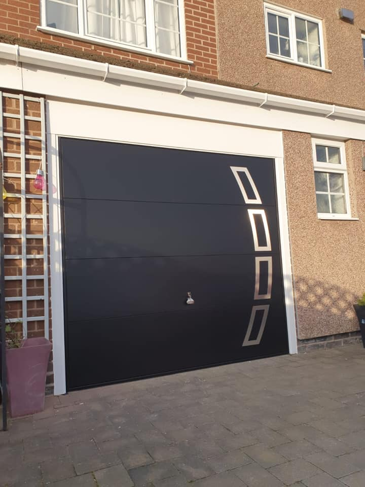 Garador up and over canopy framed garage door featuring a silver pattern design, powder coated black with a white frame to finish.
