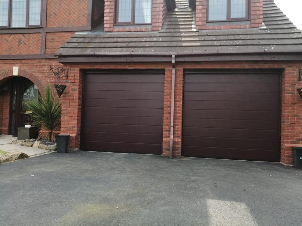 2 x Electrically operated Alutech sectional garage doors in an M-Ribbed design, finished in the Rosewood colour.