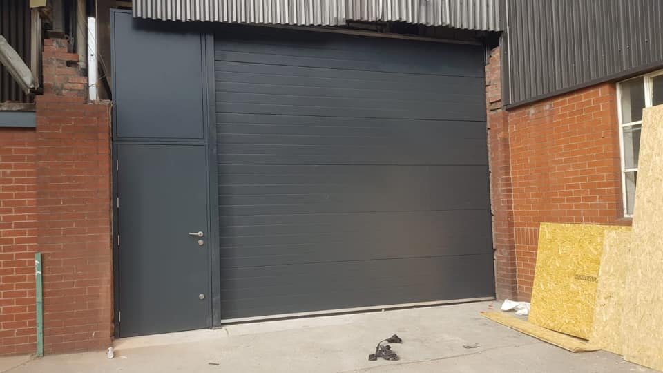 Industrial sectional door in anthracite grey with a 3 phase motor, complete with steel fire door also fitted in anthracite grey with a release push button on the inside.