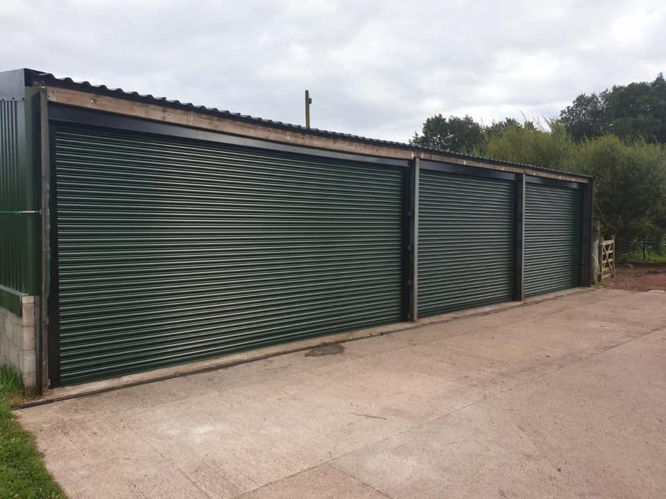 3 x industrial roller shutters in fir green with black guides, fascia and hood. Door 1 & 3 are operated via rocker switch and door 2 is operated via remote unit.