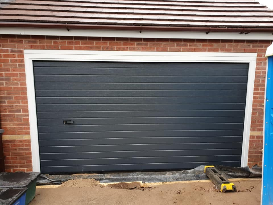 An anthracite grey Alutech sectional garage door in the S-ribbed design, wood-grain effect with white tracks