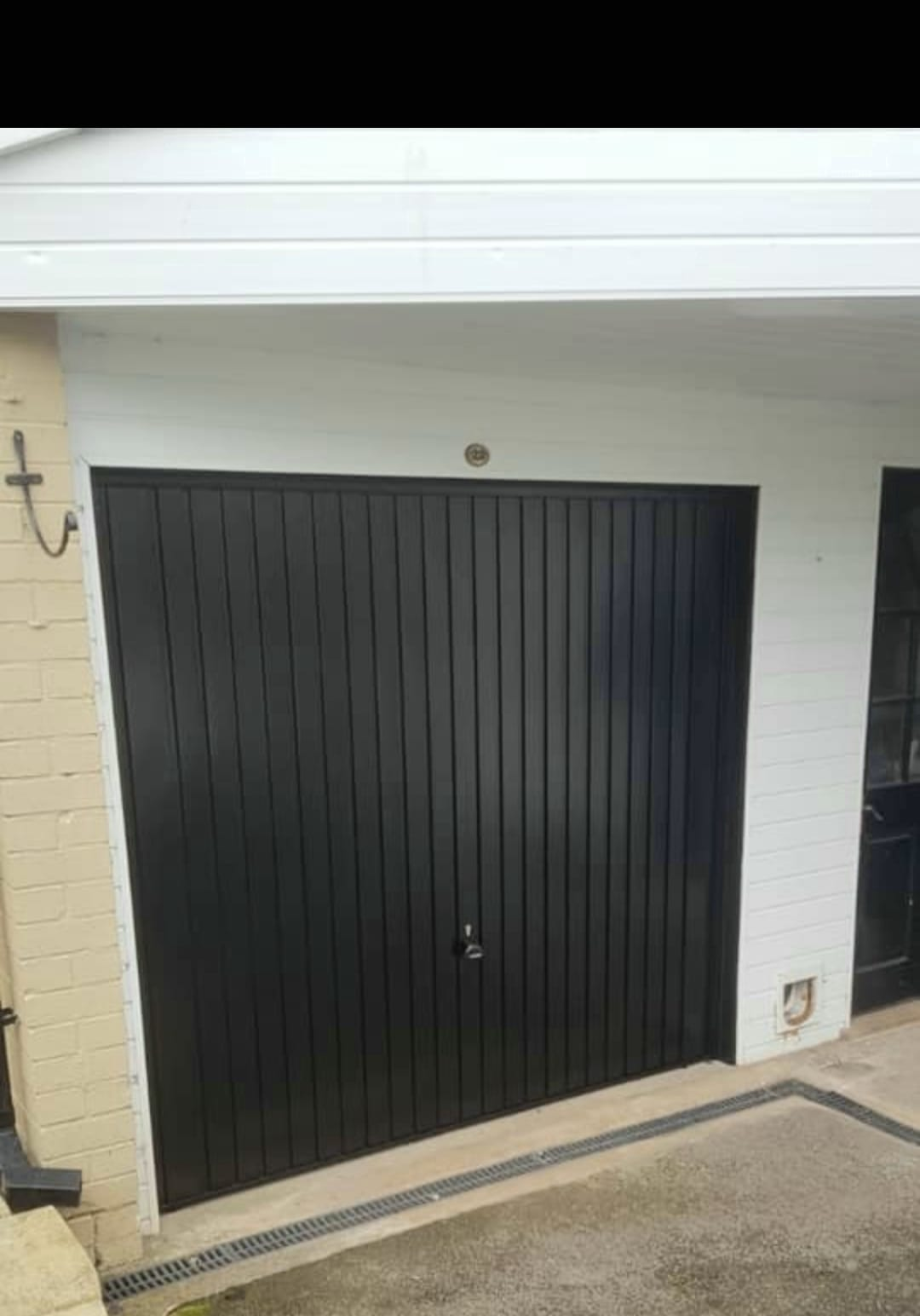 Garador canopy framed up and over garage door in the standard vertical ribbed design, powder coated black with a matching frame to finish.
