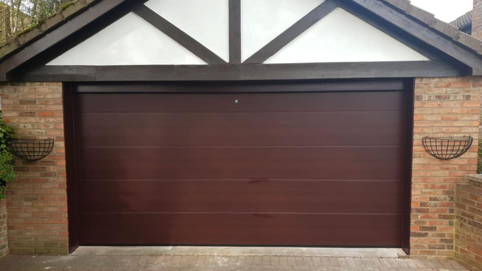 Double Alutech sectional garage door in the L-Ribbed design, with a rosewood effect. Door has an external release kit, complete with a NRG black edition motor and 2 x remote controls.