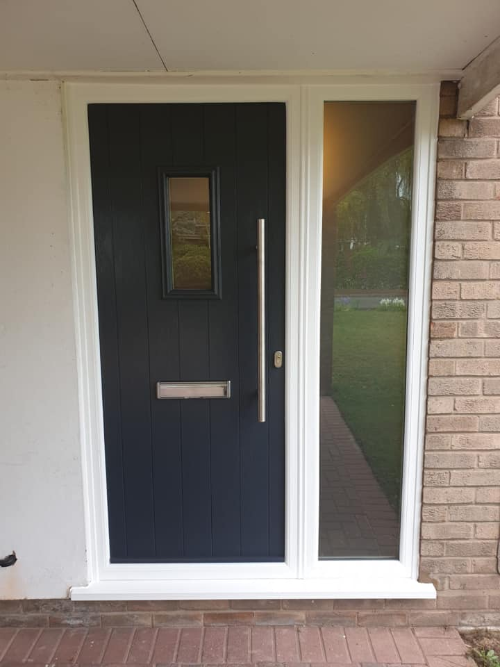 Anthracite grey Solidor composite entrance door with a side panel and white frame to finish.