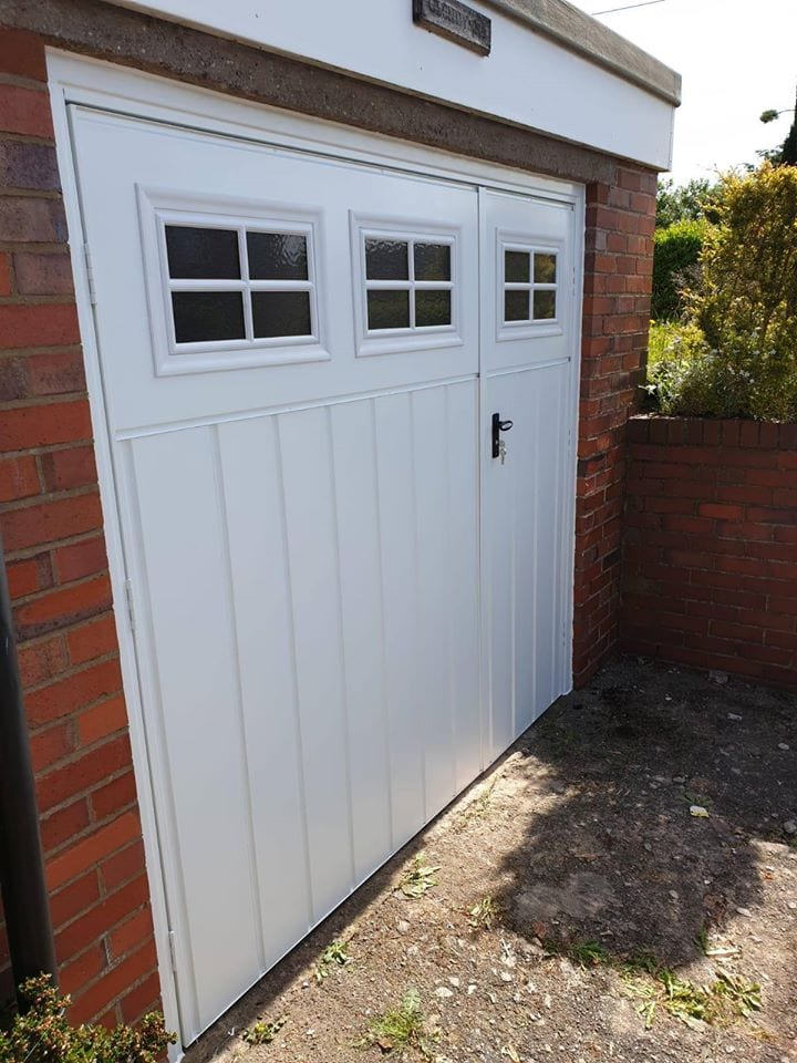Fort side hinged garage door in white with matching white frame, Medium ribbed vertical pattern finished with Stockton Windows.