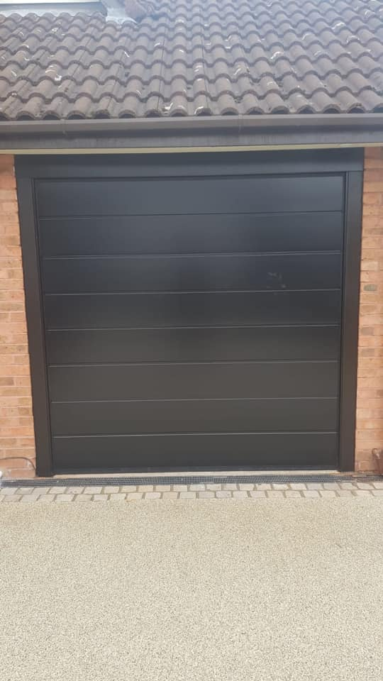 Electrically operated Insulated Alutech sectional garage door. M-Ribbed pattern finished in black smooth effect and matching colour tracks complete with NRG Black Edition motor and 2 remote controls.