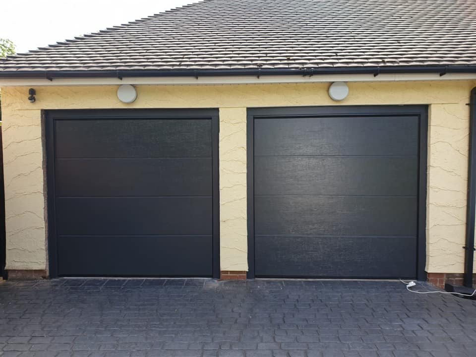 Electrically operated Alutech sectional garage door in L-ribbed pattern finished in Anthracite Grey, wood grain effect complete with NRG Black Edition motor and 2 x remote controls