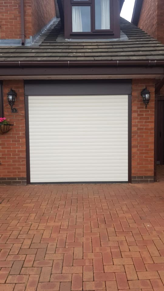 Electrically operated stylish roller door in cream with a rosewood kit, complete with 2 remote controls