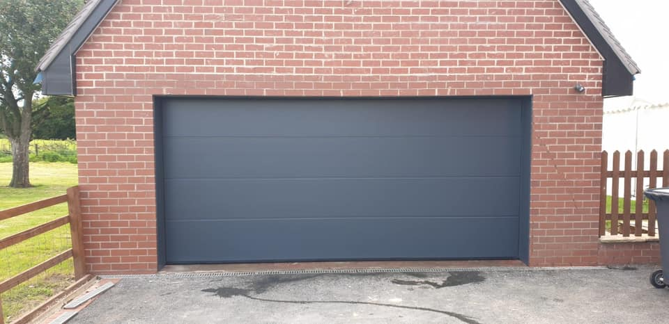 Alutech, L-ribbed sectional garage door in anthracite grey with a smooth finish. Electrically operated via a sectional motor complete with 2 remote handsets.