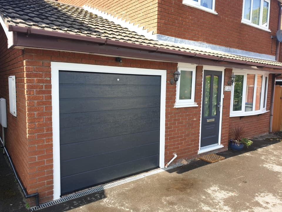 Alutech - anthracite grey sectional garage door in the M-ribbed design with a woodgrain finish.