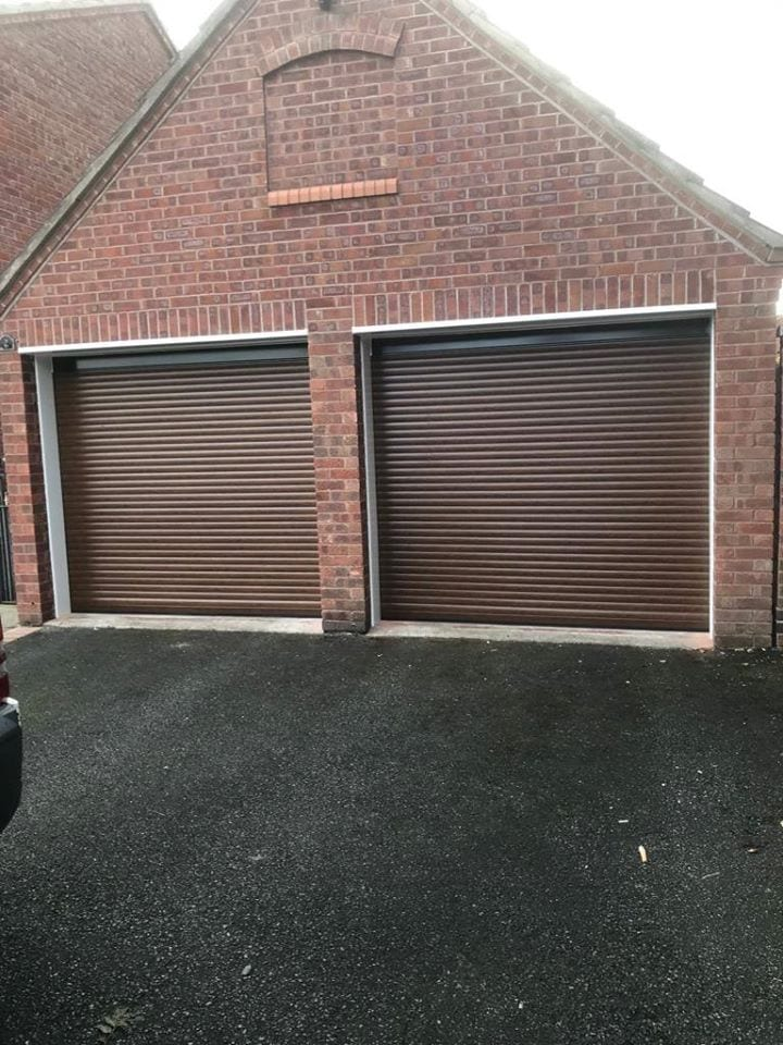 2 x 77mm electrically operated stylish roller doors in wallnut with brown kits. Both doors are operated on remote controls. Finished with PVC all around the opening.