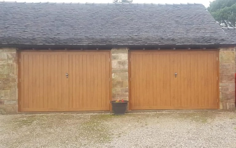 2 x fort side hinged garage doors in golden oak with matching frames, in a Drayton vertical design with a 50/50 split. Both doors are manually operated with standard black handles.