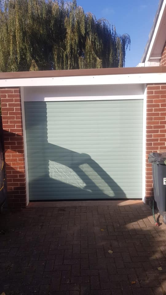Electrically operated stylish roller door in chartwell green with a white kit to finish.