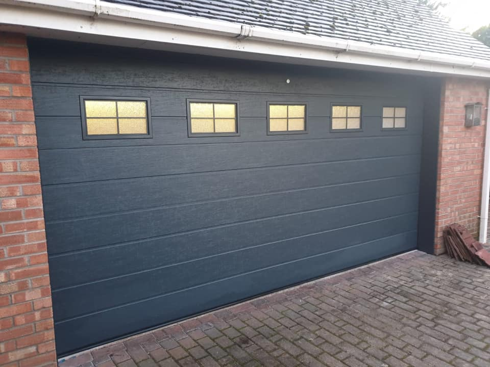 1 x Alutech sectional garage door, M-ribbed design in anthracite grey with a wood-grain finish. This door is electrically operated via 1 x sectional door motor, complete with 2 x remote handsets. Door includes 5 cross windows with frosted glass.