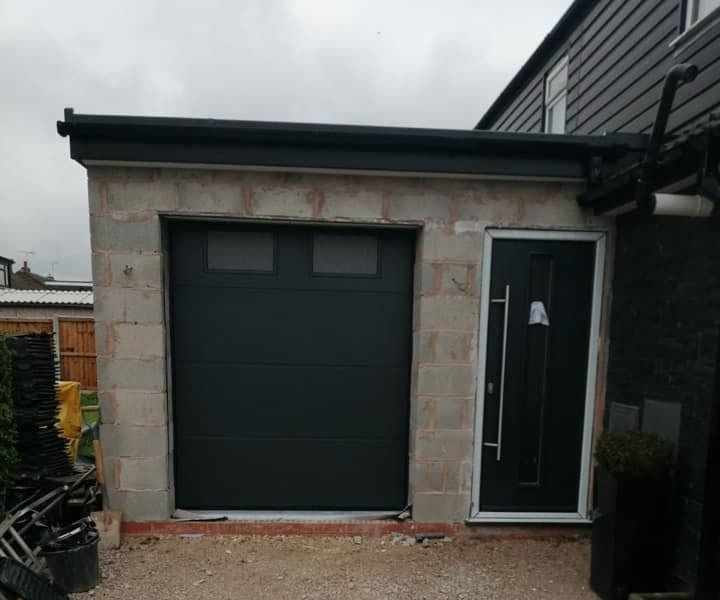 Alutech - anthracite grey sectional garage door in the L-ribbed design with a smooth finish. This door includes 2 x rectangle frosted glass windows. Door is electrically operated via 1 x sectional motor, complete with 2 x remote handsets.