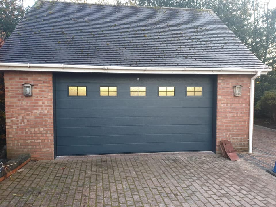 Alutech sectional garage door, M-ribbed design in anthracite grey with a wood-grain finish. This door is electrically operated via 1 x sectional door motor, complete with 2 x remote handsets. Door includes 5 cross windows with frosted glass.