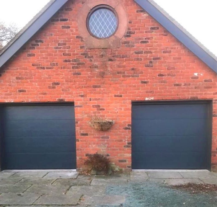 2 x Anthracite grey, Alutech sectional garage doors in an L-ribbed design with a wood-grain effect and matching colour tracks.